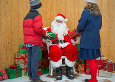 Junge und Mädchen, die Geschenke von Sankt empfangen Lizenzfreie Stockfotos