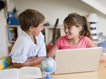 Junge und Mädchen, die ihre Heimarbeit auf einem Laptop tun lizenzfreies stockfoto