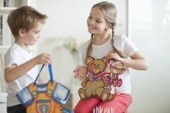 Junge und Mädchen, die ihre Spielzeugtaschen halten lizenzfreies stockfoto