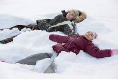 Junge und Mädchen, die im Schnee liegen Lizenzfreie Stockfotos