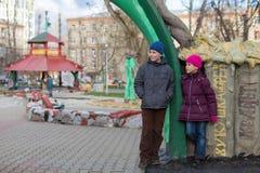 Junge und Mädchen, die im Spielplatz mit Skulpturen spielen Stockfoto
