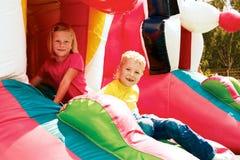 Junge und Mädchen, die im Vergnügungspark spielen Stockbild
