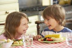 Junge und Mädchen, die Mahlzeit in der Küche essen lizenzfreies stockfoto