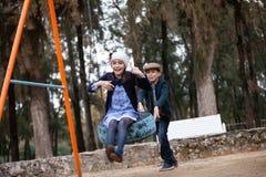 Junge und Mädchen, die mit einem Schwingen in einem Spielplatz spielen stockfotografie