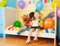 Junge und Mädchen, die mit Hund und Geschenk sitzen Lizenzfreie Stockbilder