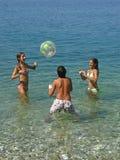 Junge und Mädchen, die mit Kugel auf Meer spielen Stockbild