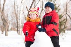 Junge und Mädchen, die mit Schnee im Winterpark spielen lizenzfreie stockfotografie