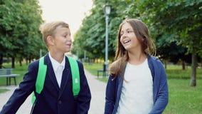 Junge und Mädchen, die mit Schultaschen gehen stock video footage