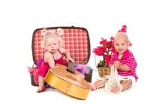 Junge und Mädchen, die nahe einem Koffer, eine Gitarre spielen Lizenzfreie Stockfotografie