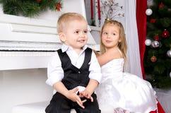 Junge und Mädchen, die nahe weißem Klavier sitzen Stockfotos