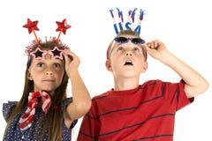 Junge und Mädchen, die oben den Feuerwerken tragen patriotische Gläser betrachtet Stockbild