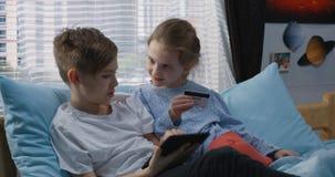 Junge und Mädchen, die online kaufen lizenzfreies stockfoto
