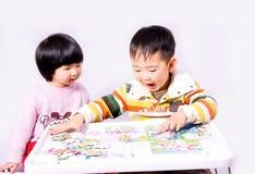 Junge und Mädchen, die Puzzlespielspiele spielen Stockbilder