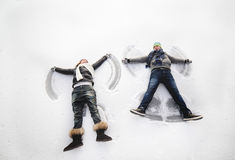 Junge und Mädchen, die Schneeengel machen Stockfoto