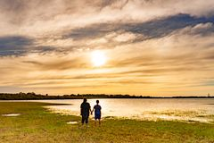 Junge und Mädchen, die Sonnenuntergang betrachten stockfotografie