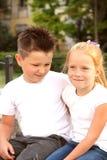 Junge und Mädchen, die umfassend sitzt Stockfotos