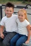 Junge und Mädchen, die umfassend sitzt Stockbild