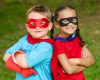 Junge und Mädchen, die vortäuschen, Superhelden zu sein stockbild