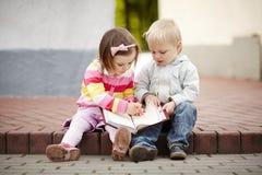 Junge und Mädchen, die zum Notizbuch schreiben Stockfoto