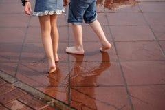 Junge und Mädchen, Ferien zusammen Pfützen, Regen lizenzfreies stockbild