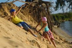 Junge und Mädchen gehen den Sand zum Strand hinunter Abenteuer, Reise, Tourismuskonzept lizenzfreies stockfoto