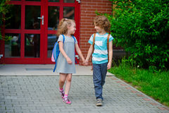 Junge und Mädchen gehen zur Schule, die Händen angeschlossen wird Stockbilder