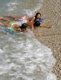 Junge und Mädchen im Schaumgummi der Wellen Lizenzfreies Stockfoto