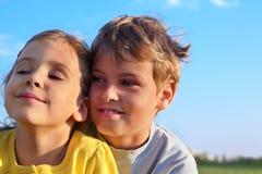 Junge und Mädchen lächeln und blicken in Richtung Stockfotos