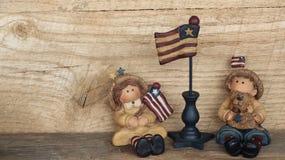Junge und Mädchen mit amerikanischen Flaggen auf hölzernem Hintergrund lizenzfreies stockbild