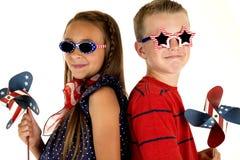 Junge und Mädchen mit patriotischen Windmühlen und Gläsern Lizenzfreie Stockfotos