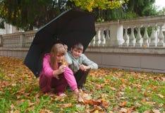 Junge und Mädchen sitzen unter einem Regenschirm Lizenzfreie Stockfotografie