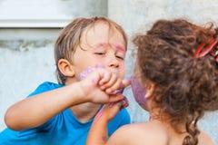 Junge und Mädchen spielen mit Gesichtsfarben Lizenzfreies Stockbild