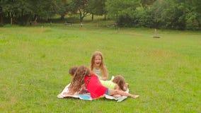 Junge und Mädchen spielen Twister im Park auf dem Gras nahe den Bäumen Langsame Bewegung stock footage