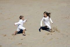 Junge und Mädchen spielen zusammen am Strand Stockfotos