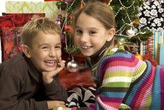 Junge und Mädchen vor Weihnachtsbaum Lizenzfreie Stockfotos