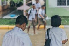 Junge und Mädchen warten, um überschwemmte Straße im schweren Regensturm zu kreuzen sind stockbild