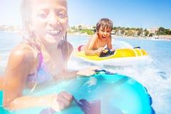 Junge und Mädchen, welche die Welle auf Luftmatrazen reiten stockbilder