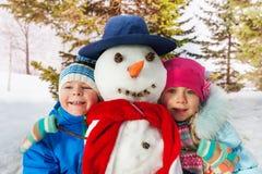 Junge und Mädchen zusammen mit gekleidetem Schneemann Stockfotos