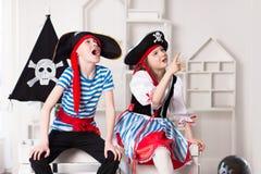 Junge und M?dchen, die Piraten spielen Sie tragen Piratenkost?me stockbild