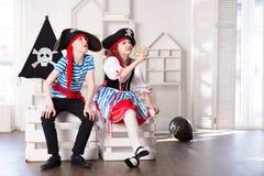 Junge und M?dchen, die Piraten spielen Sie tragen Piratenkost?me lizenzfreie stockbilder