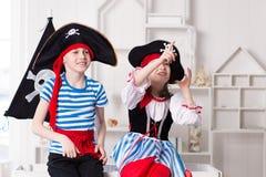 Junge und M?dchen, die Piraten spielen Sie tragen Piratenkost?me stockfotografie