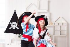 Junge und M?dchen, die Piraten spielen Sie tragen Piratenkost?me stockfoto