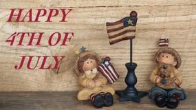 Junge und M?dchen mit amerikanischen Flaggen auf h?lzernem Hintergrund lizenzfreie stockfotografie