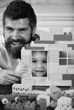 Junge und Mann auf defocused Hintergrund Vati- und Kinderfell hinter dem Haus gemacht von den Plastikblöcken Lizenzfreie Stockfotografie