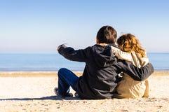 Junge und Mädchen auf dem Sandzeigen Stockbilder
