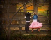 Junge und Mädchen auf Zaun Stockfotografie