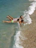 Junge und Mädchen, die auf Wellen spielen Stockbild
