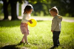 Junge und Mädchen, die mit gelbem Ball spielen Lizenzfreie Stockfotografie