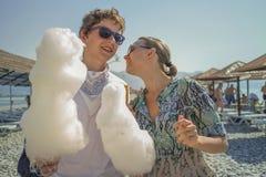 Junge und Mädchen, die Zuckerwatte am Strand essen Stockbilder