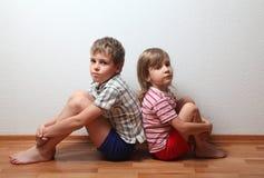 Junge und Mädchen, die zurück zu Rückseite sitzen Lizenzfreies Stockfoto